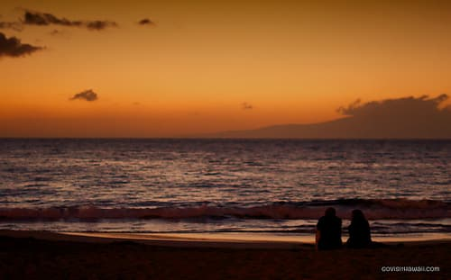 couple enjoy the post sunset sky at wailea beach